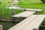 wooden bridge zigzagging a pond in Japanese garden © danysharipova
