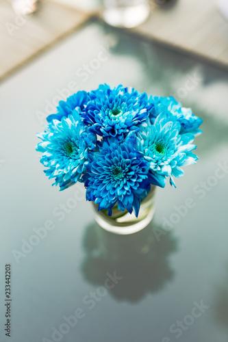 bukiet kwiatów w szklanej wazonie na niebieskim tle