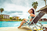 Woman on a lounger by the pool - 233455814