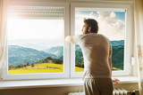 Man standing by the window and enjoying landscape