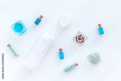 Foto Murales Sea salt for spa and aroma spa cosmetics near towel and shells on white background top view