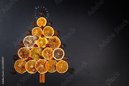 Christmas tree made of dried oranges, cinnamon and star anise on dark background. Viewed from above.