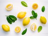 Fresh lemons and  lemons leaves on white wooden background. - 233503670