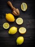 Fresh lemons and  lemons leaves on shabby wooden background. - 233503696