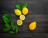 Fresh lemons and  lemons leaves on dark wooden background. - 233503805