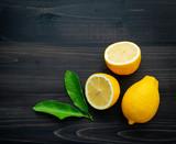 Fresh lemons and  lemons leaves on dark wooden background. - 233503834