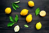 Fresh lemons and  lemons leaves on dark wooden background. - 233503837