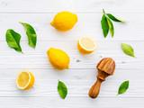Fresh lemons and  lemons leaves on white wooden background. - 233503864