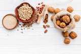 Various legumes and different kinds of nuts set up on white wooden table. - 233503884