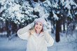 Winter portrait of a smiling woman in a hat and mittens. New Year