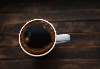 black coffee in white Cup on brown background