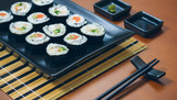 Sushi maki rolls presented on a tray with sauces and chopsticks © David Pereiras
