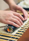 Closeup of woman chef hands rolling up japanese sushi with rice, avocado and crab sticks on nori seaweed sheet - 233516018