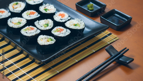 Sushi maki rolls presented on a tray with sauces and chopsticks