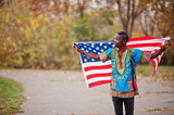 African man in africa traditional shirt on autumn park with USA flag. - 233523266
