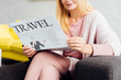 close up of mature woman sitting on sofa and reading travel newspaper