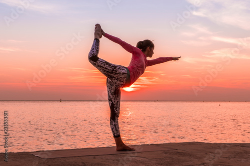Fototapeta Young beautiful woman practicing Yoga by the sea at sunset