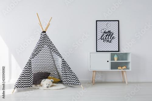Wzorzyste czarno-biały namiot skandynawski z szarymi i żółtymi poduszkami i białym misiem obok drewnianej szafki z plakatem w czarnej ramie, miejsce na pustej białej ścianie