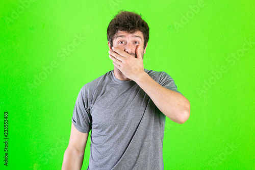 portrait of young man covering his mouth with hand over green background. - 233553483
