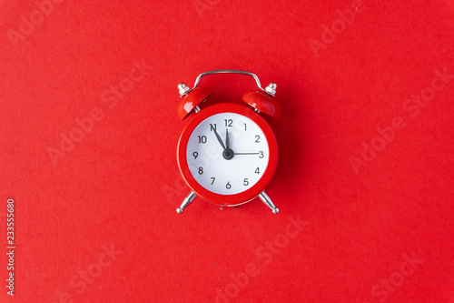 fototapeta na ścianę Creative flat lay vintage clock on red office table top view background concept clock on red paper color with copy space in minimal style, empty template for text, break workplace at noon for lunch.