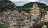 Panorama of Scicli -  a fascinating and beautiful town built in a style of Sicilian Baroque. The view of the city Scicli with the Church of Saint John the Saint Johnt at the background. - 233556299