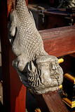 wooden carved decoration shaped as a marine monster on the handrail of an ancient ship