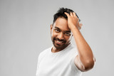 grooming and people concept - smiling young indian man touching his hair over gray background