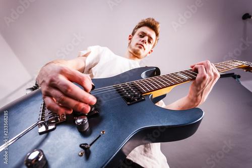 Młody człowiek gra na gitarze elektrycznej