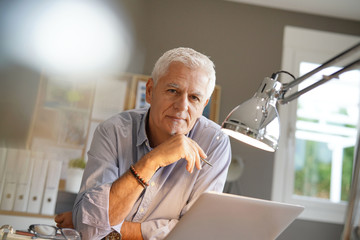 Mature man working in office, looking at camera