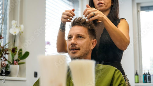 A man getting his hair cut by a woman hairdresser with tatoos