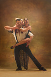 Flexible young modern couple dancing tango in studio. Fashion portrait of attractive dancing couple. Man and woman. Passion. Love. perfect skin facial and make-up. Human emotions - love and passion - 233572088