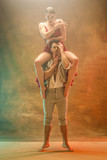 Flexible young modern couple dancing tango in studio. Fashion portrait of attractive dancing couple. Man and woman. Passion. Love. perfect skin facial and make-up. Human emotions - love and passion - 233572249