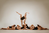 The group of modern ballet dancers dancing on gray studio background - 233572839