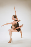 The two modern ballet dancers dancing on gray studio background - 233572874
