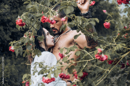 Foto Murales Spring couple. Sensual couple in Blooming flowers in orchard. Couple hugging and kissing. Valentines day concept. First date and flirt.