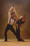 Flexible young modern couple dancing tango in studio. Fashion portrait of attractive dancing couple. Man and woman. Passion. Love. perfect skin facial and make-up. Human emotions - love and passion - 233574630