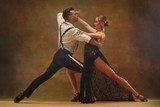 Flexible young modern couple dancing tango in studio. Fashion portrait of attractive dancing couple. Man and woman. Passion. Love. perfect skin facial and make-up. Human emotions - love and passion - 233574639