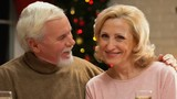 Old man tenderly kissing wife, celebrating Xmas, happy together till old age - 233578679
