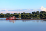 Tugboat pulling heavy loaded barge of black coal along the green trees on the shore of Danube river - 233579811