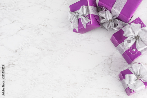 Bożenarodzeniowi purpurowi prezenty z srebnym faborkiem na marmuru stole