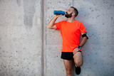 Man resting from running and drinking water while standing against the wall. Healthy lifestyle concept. - 233594274