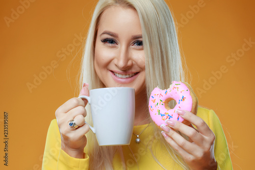 Sticker Close up portrait of a smiling girl in yellow dress posing with donuts and cup of coffee at her face isolated over yellow background