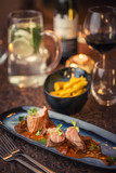 grilled pork tenderloin with mushroom sauce served on plate with glass of wine and dumplings, modern seasonal gastronomy - 233603264