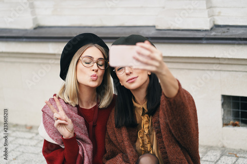 Foto Murales Two attractive girls making selfie while sitting together