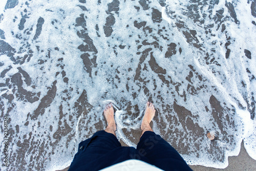 Foto Murales Blue waves in the sand with male feet