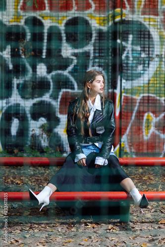 Photo model wearing white high-heeled boots posing near graffiti