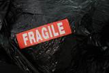 fragile emballage étiquette signalétique attention rouge emballer sac plastique cello film noir envoyer transport - 233613617