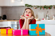 beautiful white girl with a gift boxes sitting at table against the background of the scenery for Christmas in the kitchen