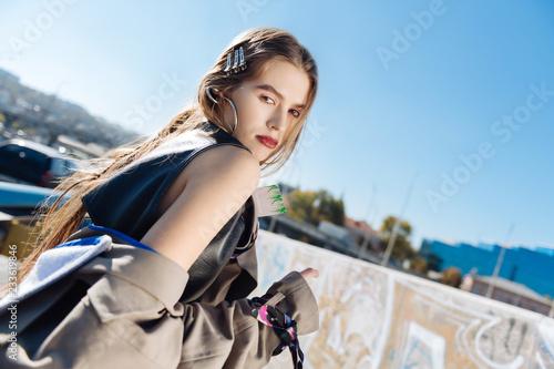 Ciemnooka modelka z trzema prowadnicami do włosów w beżowym płaszczu