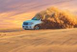 Off-road adventure with SUV in Arabian Desert at sunset. Offroad vehicle bashing through sand dunes in Dubai desert.